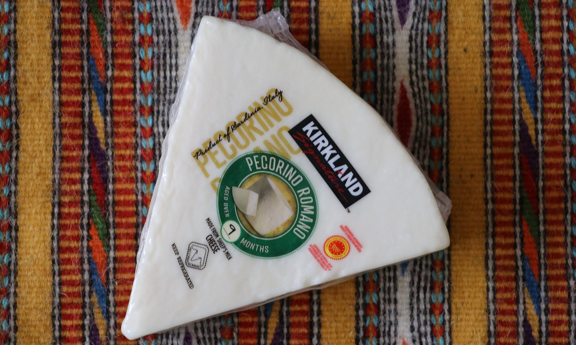 Pecorino Romano, as packaged and sold at Costco. Shown on a handwoven textile from Eugenia Pinna, from Nule, Sardegna.